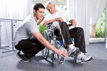 junger Mann assistiert Mann im Rollstuhl