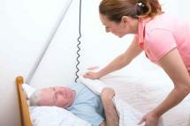 Pflegerin deckt Patienten zu