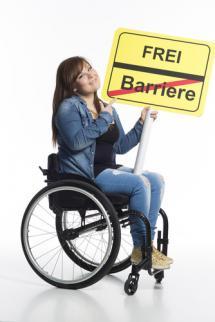 Frau im Rollstuhl sitzend hält ein gelbes Schild mit schwarzem Trennstrich in der Mitte. Oben steht frei, im unteren Teil Barrieren