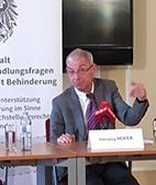 Dr. Hansjörg Hofer hinter einem Tisch sitzend, vor ihm ein weisses Schild mit seinem Namen.