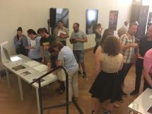 BesucherInnen stehen um einen Tisch mit Computer und betastbaren Reliefen